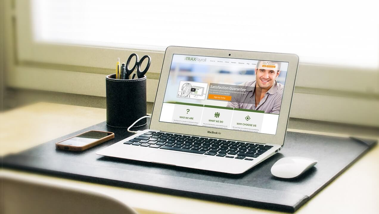 Traxpayroll website on a laptop